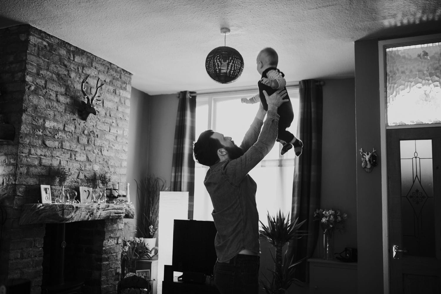 Dad playing with his son in their house in Stretford
