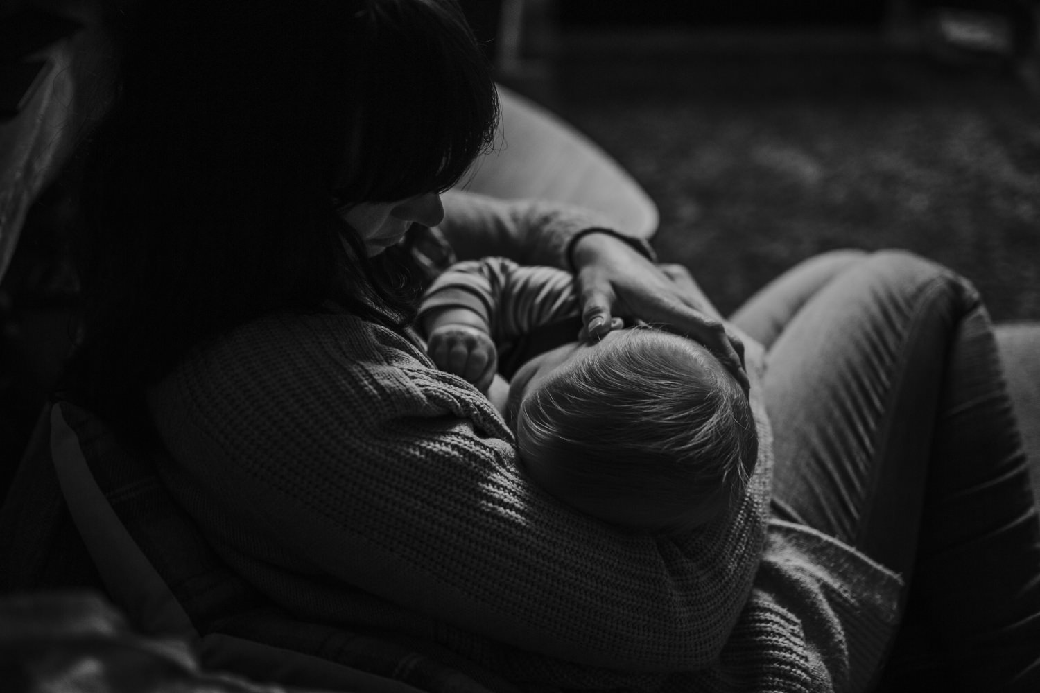 Mom breastfeeding in the couch during a snowy Day in the Life Session in Manchester