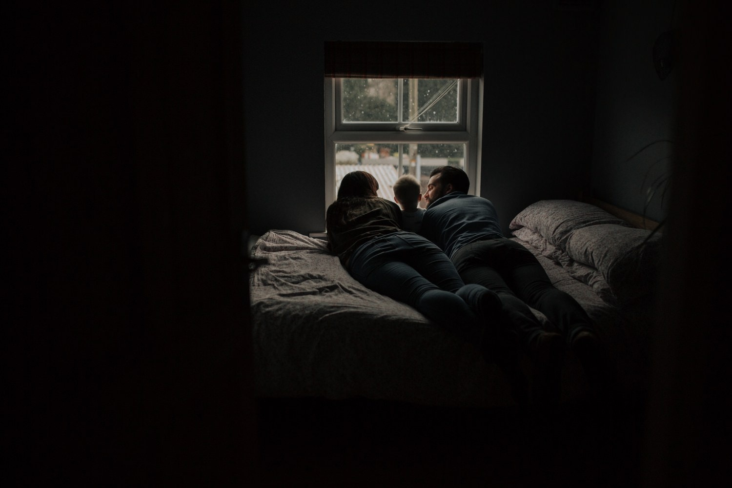 Family on the bed watching the snow falling outside