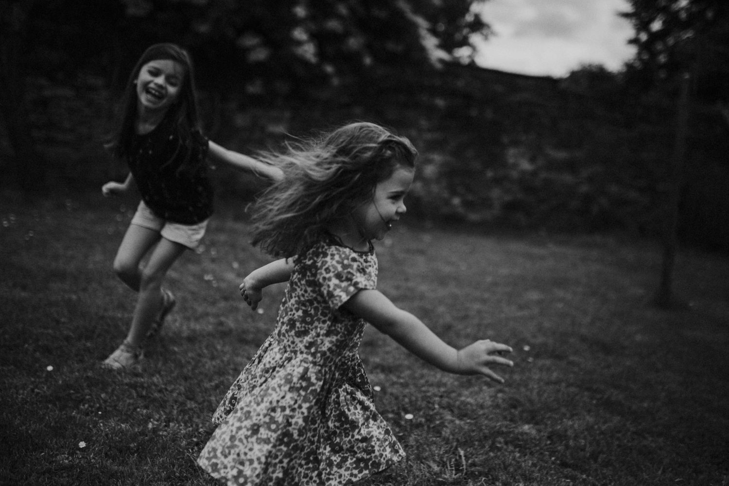 sisters running in the garden during a family session in Manchester from Like Dreamers Do's portfolio