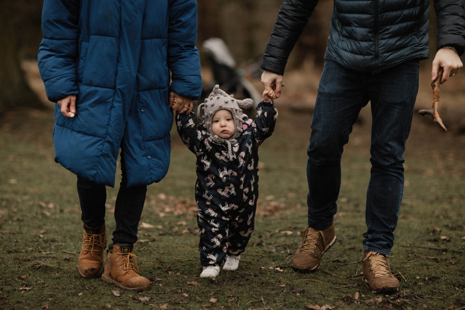Daughter doing her first steps with her parents holding her hands in Manchester