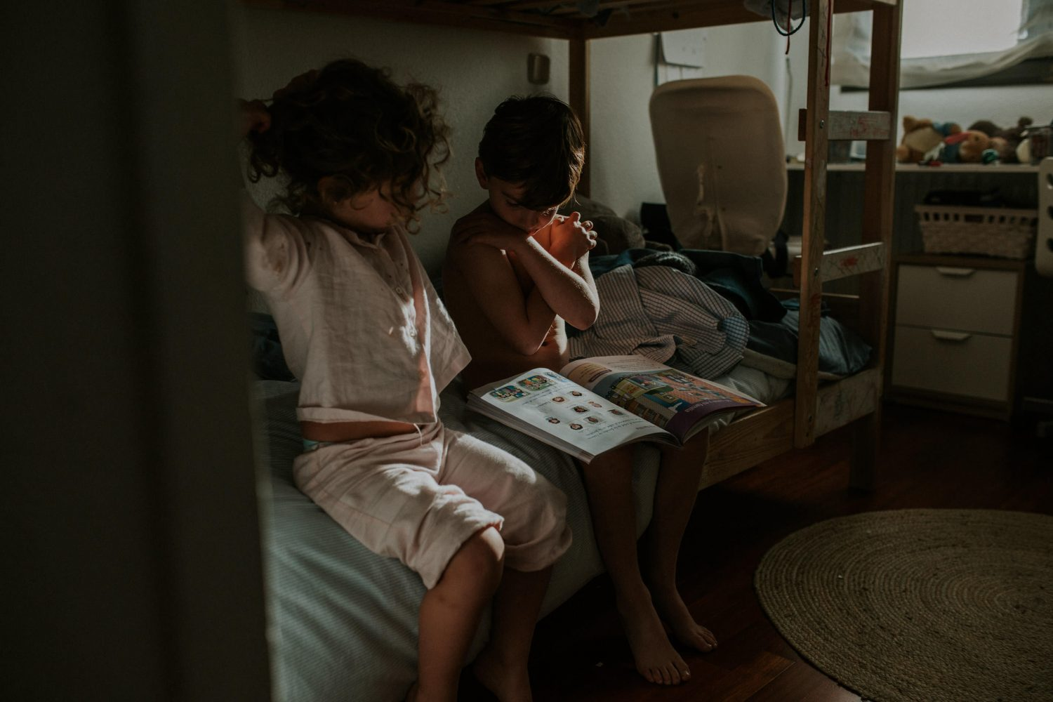 sister and brother reading a book in the morning during a documentary family session