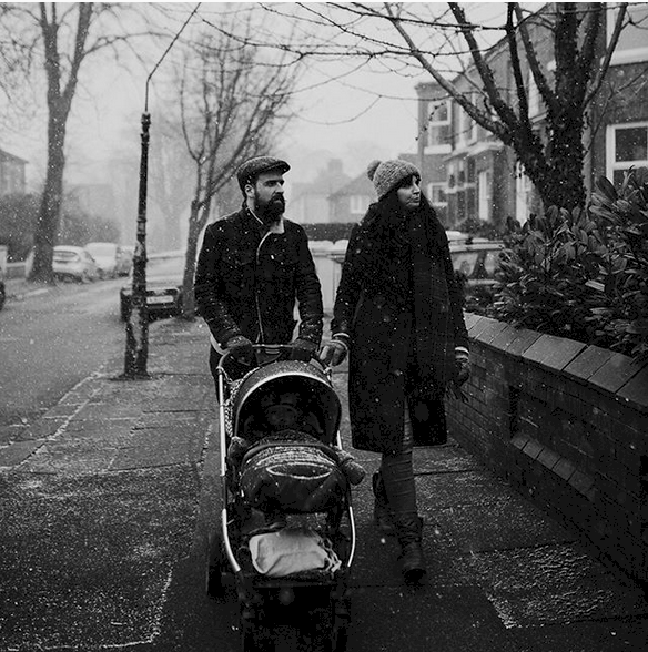 Couple walking with their baby in a pram in the snow in Chorlton Manchester