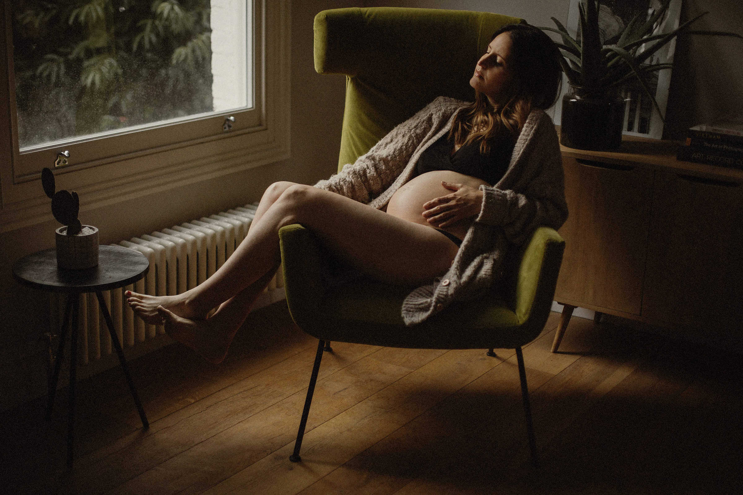 pregnant woman sat down in a contemporary chair during a winter maternity session in London